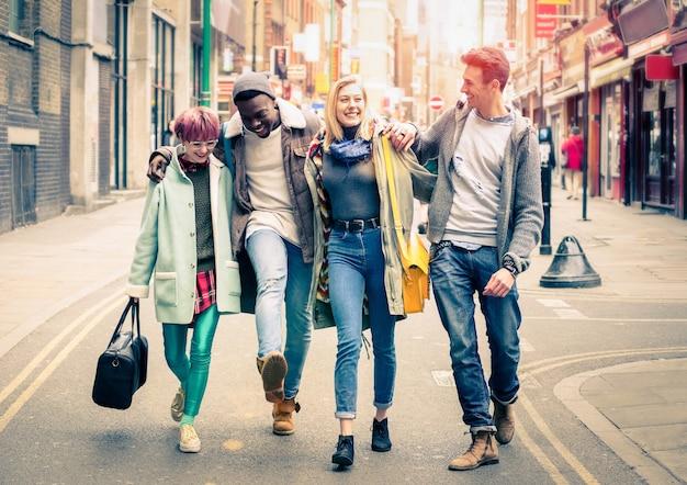 Счастливые многорасовые друзья гуляют по брик-лейн в шордич в лондоне