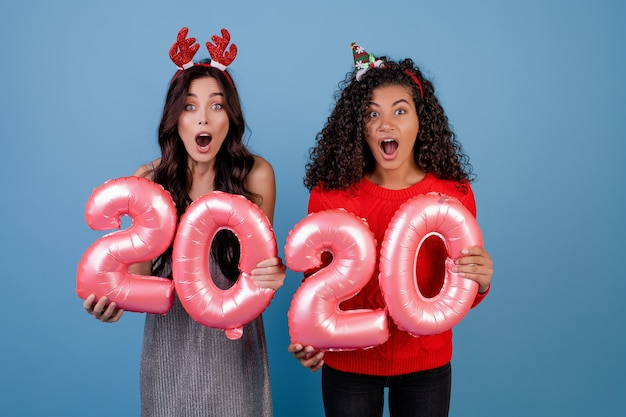 Happy multiracial girls with 2020 new year balloons and funny holiday hoops isolated over blue
