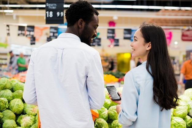 Happy multiracial pair choosing goods in supermarket