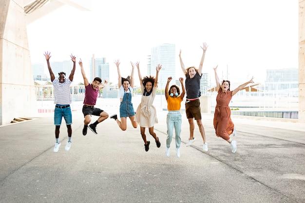 Счастливые многорасовые люди прыгают вместе на открытом воздухе