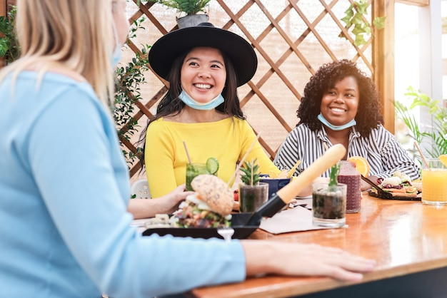 Happy multiracial young friends eating at brunch restaurant during coronavirus outbreak - focus on asian girl