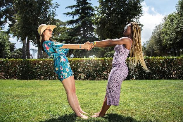 幸せな多民族の若いレズビアンのカップルが公園で手をつないでいます。遊び心のコンセプト。 lgbtの概念。