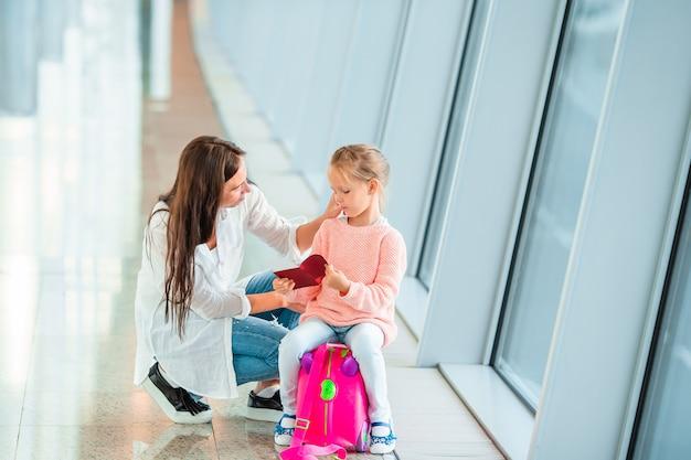幸せな母と空港で搭乗券を持つ少女