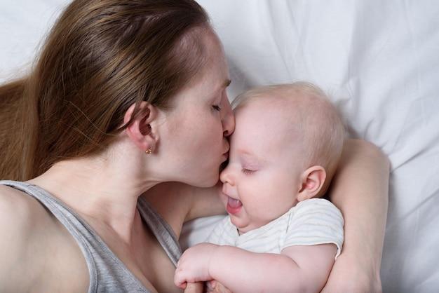 幼児の子供を手に持って幸せなお母さん。彼女の赤ちゃんにキスする美しい若い母親。