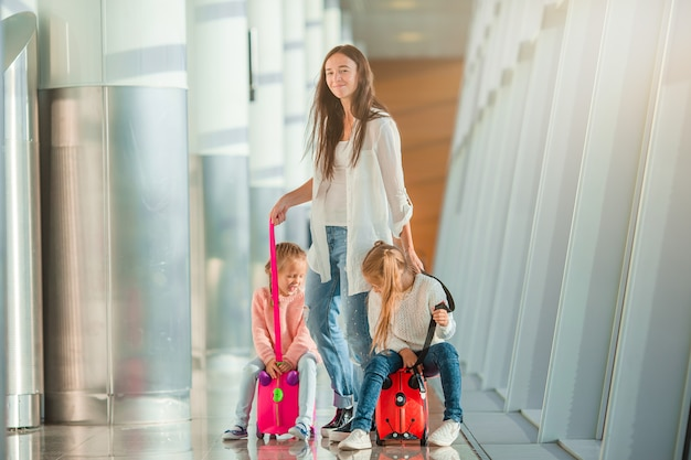 Happy mum and little girls with boarding pass at airport