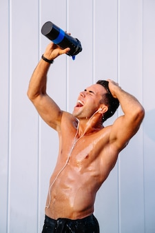 Happy muscular guy pouring out water from bottle on his body, sweating after training