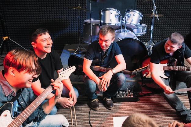 Группа счастливых музыкантов сидит с инструментами в круге