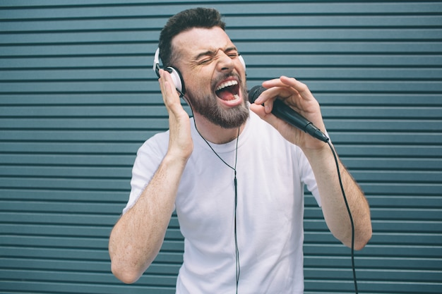 Happy musician is enjoying listening to music. he wears headphones and singing. guy is using karaoke. man is singing ot loud. isolated on striped