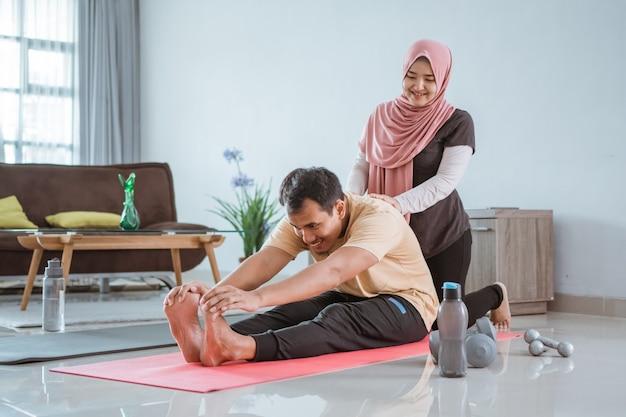 幸せなイスラム教徒のアジアのフィットネスカップル、男性と女性が家で一緒に運動