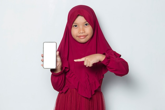 Happy muslim asian little girl  demonstrating mobile cell phone on white background