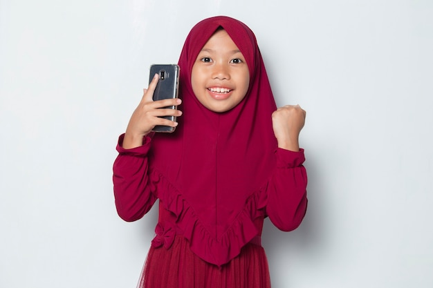 Happy muslim asian little girl using smart phone on white background