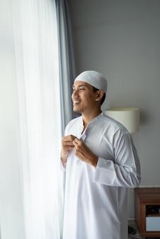 窓の近くに立っている幸せなイスラム教徒のアジア人男性は、モスクに行く前に服を着る