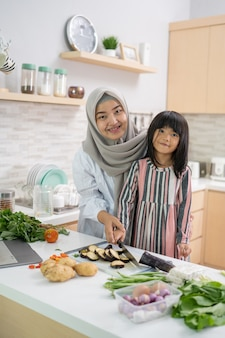 Счастливая мусульманская азиатская женщина с дочерью готовит вместе на кухне во время рамадана