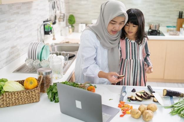 ラマダン中にキッチンで一緒に料理をしている娘と一緒に幸せなイスラム教徒のアジアの女性