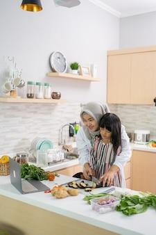 Счастливая мусульманская азиатская женщина с дочерью готовит вместе на кухне