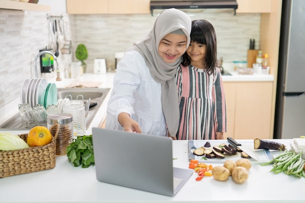 Happy muslim asian woman with her daughter cooking together in the kitchen