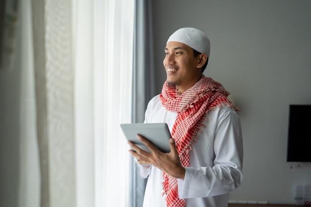 창 근처 태블릿 pc를 사용하는 동안 웃 고 행복 한 이슬람 사업가