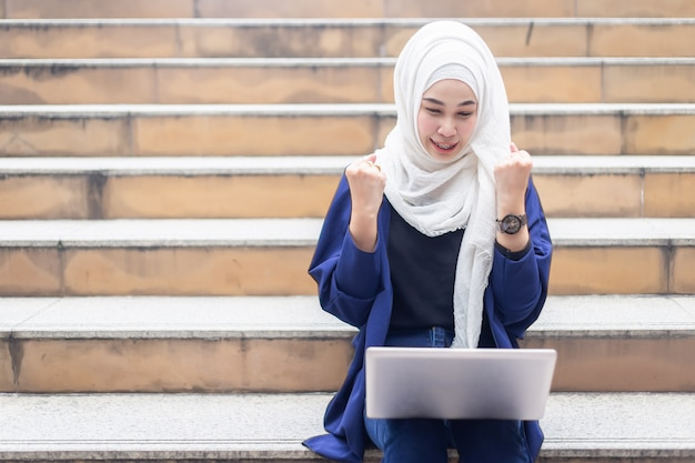 Happy muslim businesswomen in hijab with laptop working outdoors.