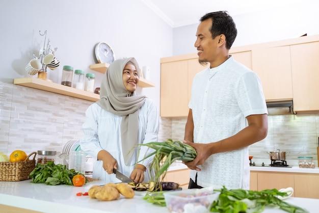 Счастливая пара мусульман, вместе готовить на кухне. мужчина и женщина готовятся к обеду