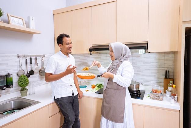 幸せなイスラム教徒のカップルがキッチンで一緒に料理します。夕食の準備をしている男性と女性