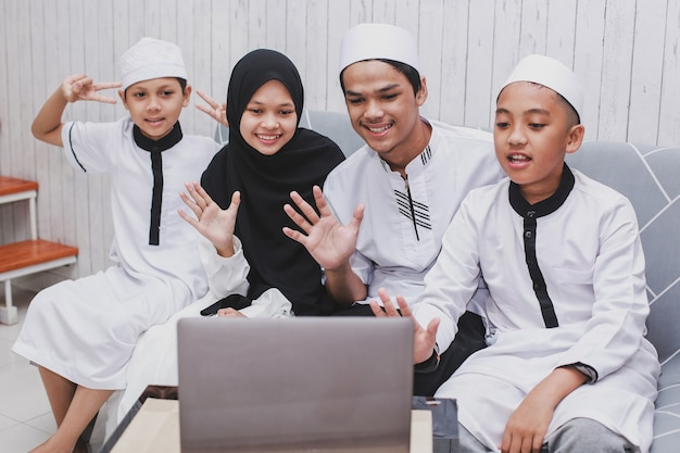 Eid 무바라크 축하 행사에서 손으로 인사하거나 인사와 함께 노트북 앞에서 화상 대화를하는 행복한 무슬림 가족
