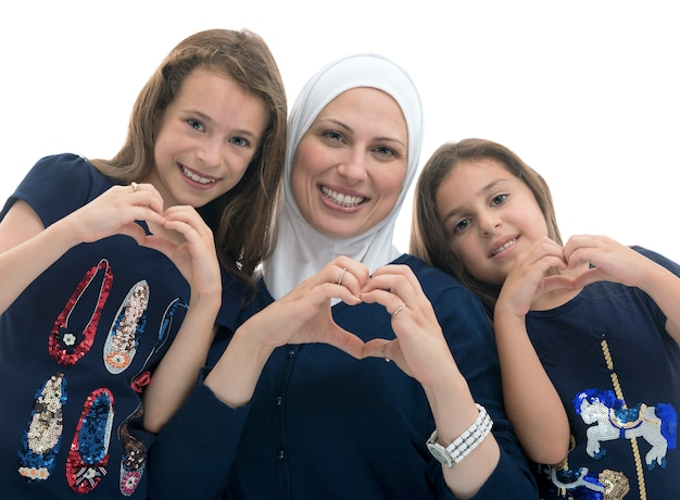 Happy muslim family, mother and her daughters with heart love sign