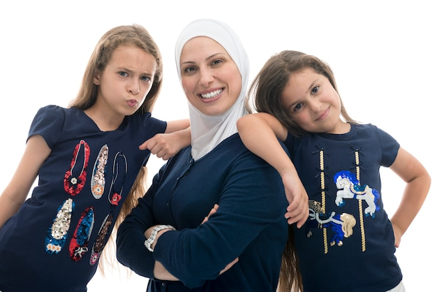 Happy muslim female family, mother and her daughters with funny pose
