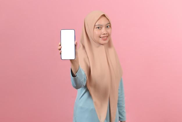 분홍색 배경에 스마트폰 디스플레이를 보여주는 행복한 이슬람 여성