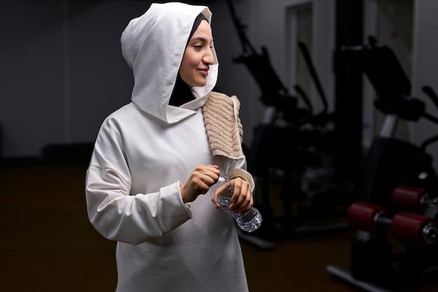 ジムで水のボトルと幸せなイスラム教徒の女性のスタンドは、笑顔で、横を見て立っています。肖像画