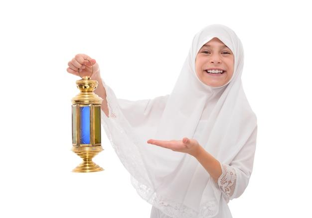 Счастливая мусульманская девушка улыбается празднует рамадан с праздничным фонарем