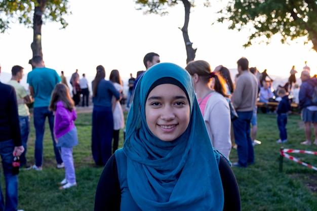 백그라운드에서 사람들과 행복 이슬람 소녀