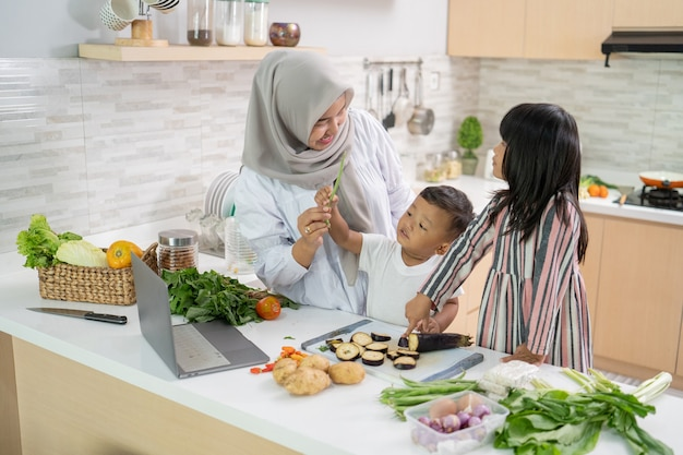 Счастливая мусульманская мать и ее дети готовят и веселятся вместе дома, готовясь к ужину ифтар