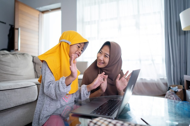 Happy muslim mother and child singing and clapping together while using laptop together
