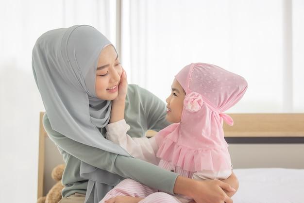 침대에 그녀의 딸과 함께 껴 안고 행복 이슬람 어머니
