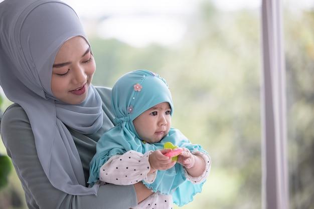 美しい小さな赤ちゃんを抱いて幸せなイスラム教徒の母親