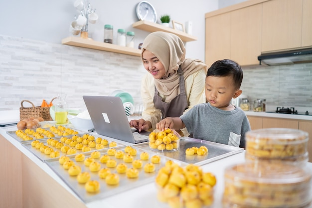 Happy muslim mother working from home making food order of nastar pineapple cake
