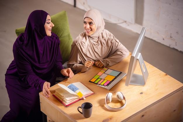 온라인 수업 중에 집에서 행복한 이슬람 여성. 기술, 원격 교육, 민족 개념