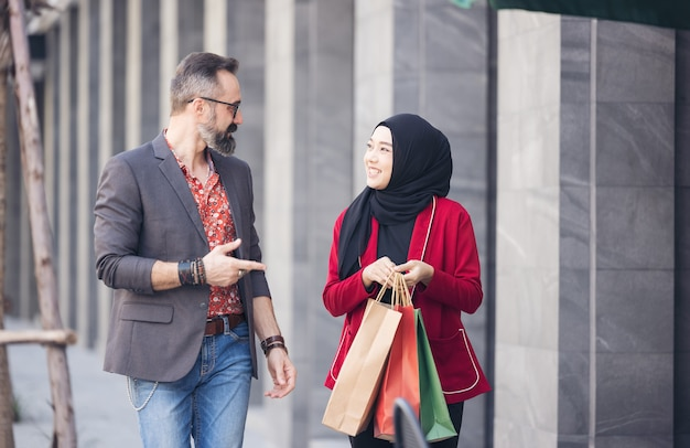 Happy muslim woman and boy freind with city shopping hand holding paper bags
