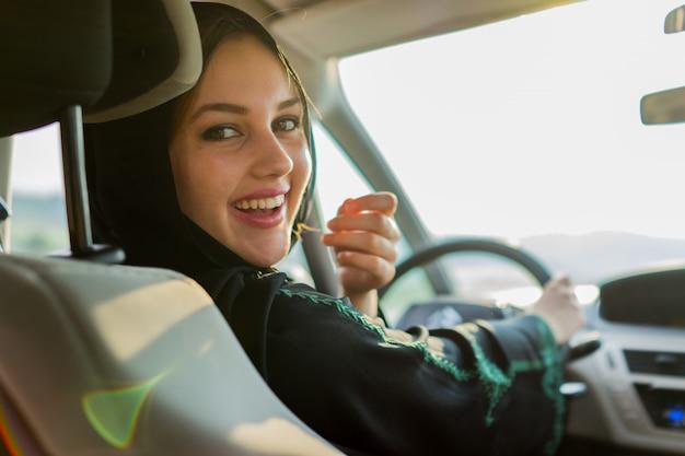 Счастливая мусульманская женщина вождения автомобиля