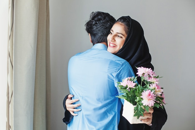 イードアルフィトルで彼女の兄弟から花を取得する幸せなイスラム教徒の女性