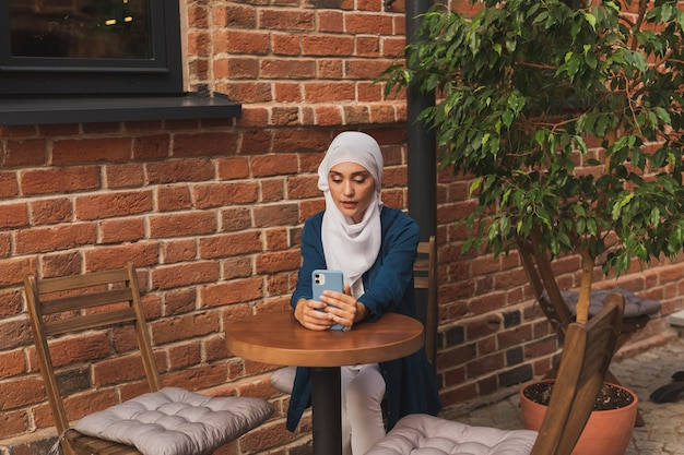 Счастливая мусульманская женщина, имеющая видеозвонок на смартфоне в городе