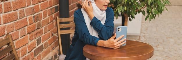 도시에서 스마트폰으로 영상 통화를 하는 행복한 이슬람 여성