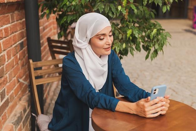 Happy muslim woman having video call on smartphone in city.