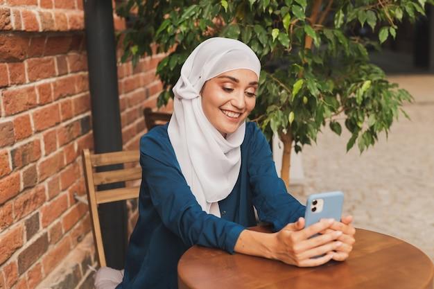 Happy muslim woman having video call on smartphone in city
