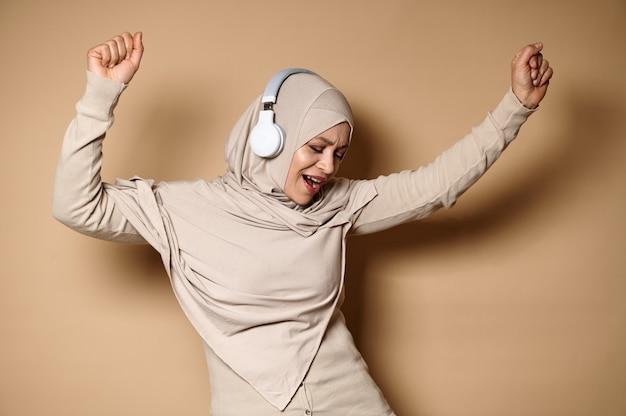 ヒジャーブとヘッドフォンで幸せなイスラム教徒の女性かわいい笑顔とリラックス、音楽を聴きながら踊る
