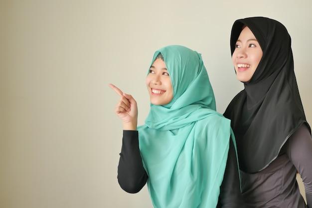 幸せなイスラム教徒の女性、上向きの笑顔のイスラムの女性。イスラム教徒の女の子が指摘します。ヒジャーブまたはヘッドスカーフの指または空白スペースに手を指している美しいアジアのイスラム教徒の女性