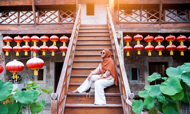 Happy muslim woman tourist sitting on a staircase in a chinese house atmosphere, asian woman  in holiday. travel concept. chinese theme.
