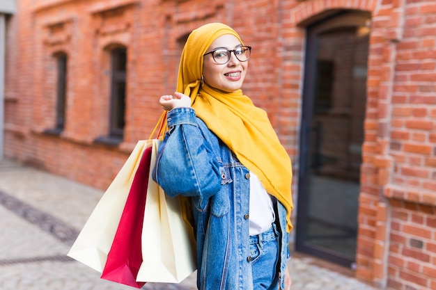 Happy muslim woman with shopping bags after mall