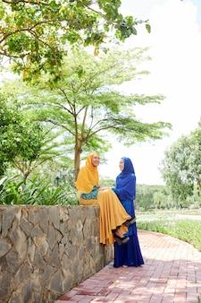 Happy muslim women resting in park