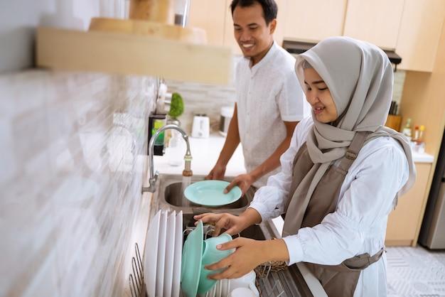 Счастливая молодая мусульманская пара моет посуду после совместного ужина ифтара в кухонной раковине